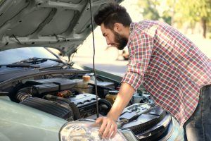Young handsome man looking under car hood